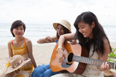 asian group: portrait group of young asian woman palying guitar in sea beach picnic party at sea side with happiness face emotion