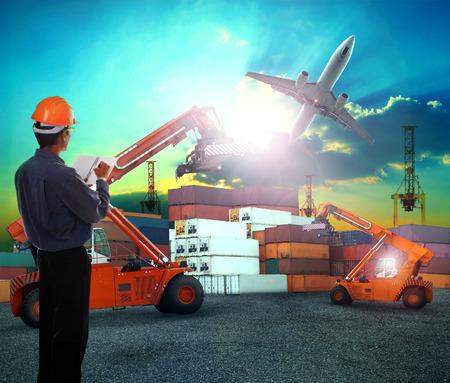 空輸輸送機そして貨物に夕暮れの空と土地使用上を飛ぶジェット飛行機貨物コンテナー出荷ヤードで働くロジスティック ビジネスで働いてる男性