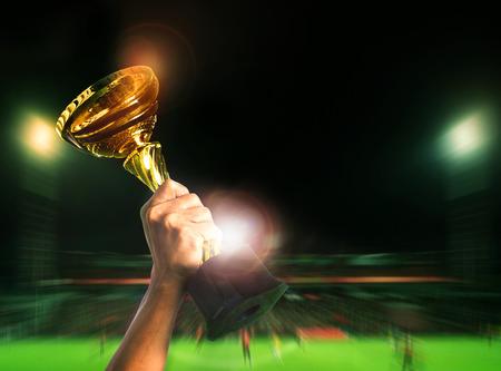 スタジアム バック グラウンドでスポーツ大会サッカー サッカー選手権カップに上昇を手します。 写真素材