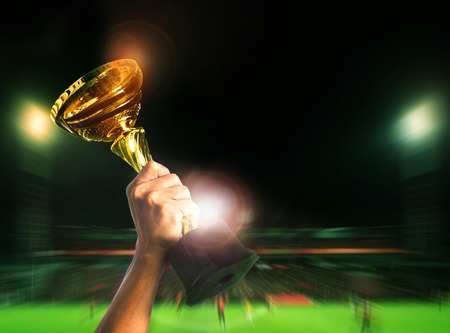 hand rising soccer football championship cup on sport competiton in stadium background Stock Photo