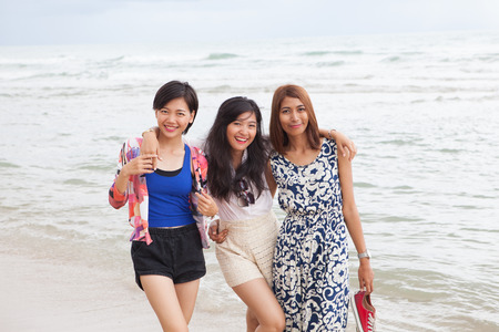frienship: portrait of young beautifu asian woman friend relaxing happy emotion on sea beach vacation holiday