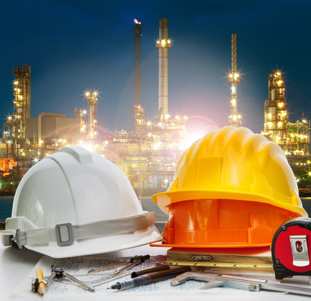 petrochemical: safey helmet on engineer working table agaisnt beautiful lighting of oil refinery in petroleum petrochemical plant use for energy ,power and fossil fuel industry