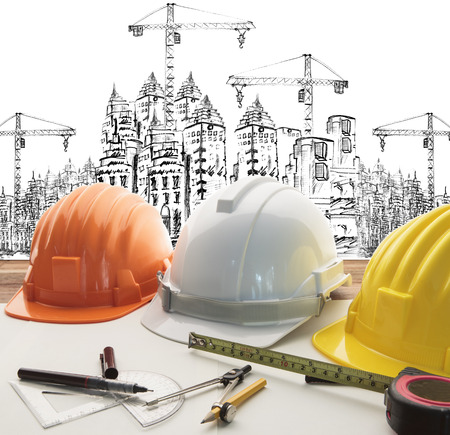 building safety: safety helmet on architect ,engineer working table with modern building and crane construction background use for construction business and civil engineering ,real estate topic Stock Photo