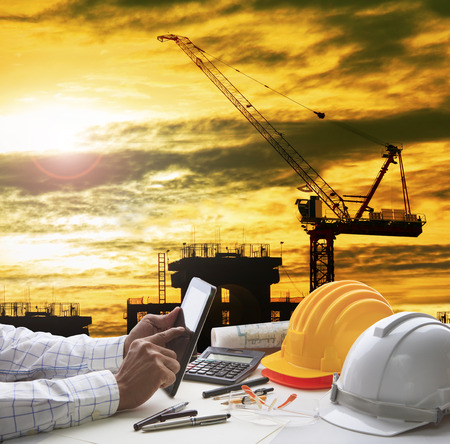 Hand des Architekten arbeiten an Computer-Tablette mit Bau- und Ingenieur-Tool oben auf dem Tisch vor zu Hause aus Linie und Skizzieren des modernen Gebäudes Perspektive