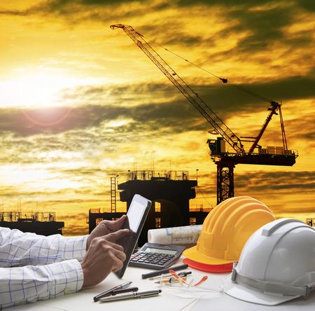 la mano del arquitecto que trabaja en la tablilla del ordenador con la industria de la construcción y herramienta de trabajo ingeniero en la parte superior de la mesa contra el hogar fuera de línea y dibujo de la perspectiva de construcción moderna