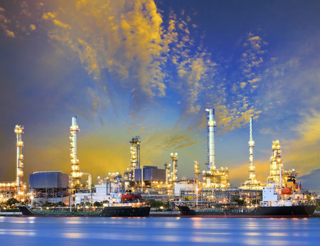 heavy fuel: tanker ship and petrochemical oil refinery industry plant with beuatiful lighting against dusky sky use for heavy industrial and energy ,fuel business