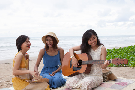 out of doors: portrait group of young asian woman playing guitar in sea beach picnic party at sea side with happiness face emotion
