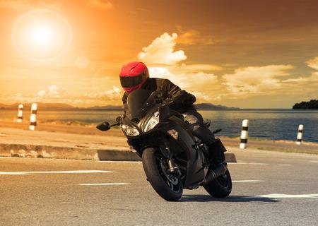 junger Mann reitet Big Bike Motorrad gegen scharfe Kurve der Asphaltstraße mit hoher Wege ländlichen Seeszene Verwendung für männliche Abenteuer und Motorsport Hobby im Urlaub Urlaub