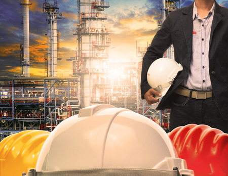 building safety: engineering man with white safety helmet standing in front of oil refinery building structure in heavy petrochemical industry Stock Photo