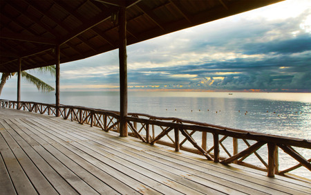 sunrise ocean: wood terrace in wooden pavillion against peaceful of heaven sea beach