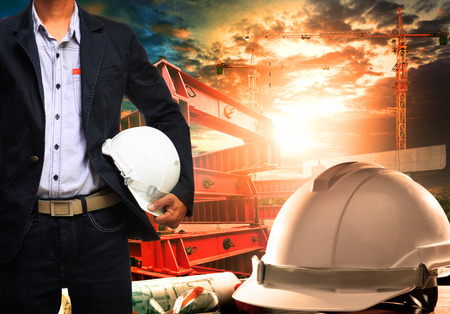 白い安全ヘルメット作業テーブルに対して立っていると建物の建設現場とエンジニアの男