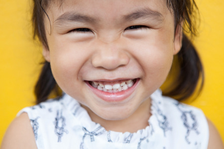 child smile: close up face of asian kid toothy smiling facial face with happiness emotion on yellow wall use for children lovely emotion and dental health theme Stock Photo