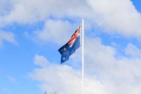 bandera de nueva zelanda: bandera de Nueva Zelanda contra hermosas nubes blancas en el cielo azul Foto de archivo