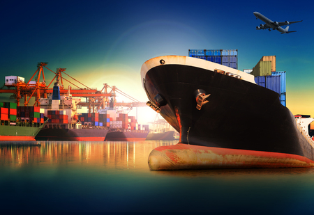 sea freight: container ship in import,export port against beautiful morning light of loading ship yard use for freight and cargo shipping vessel transport