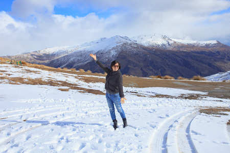 snow field: asian woman with happiness emotion standing in ice snow field in queentown south island new zealand use for traveling and tourism scene Stock Photo