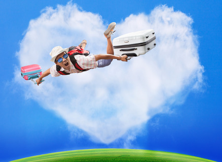 sender: hand preparing to throwing paper plane to mid air againt green grass field and heart shape white clouds on clear blue sky Stock Photo