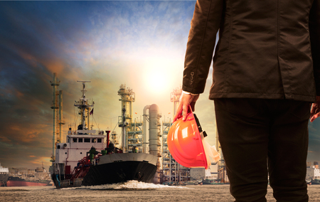 working man and oil refinery with lpg gas storage ship transport in river Stock Photo