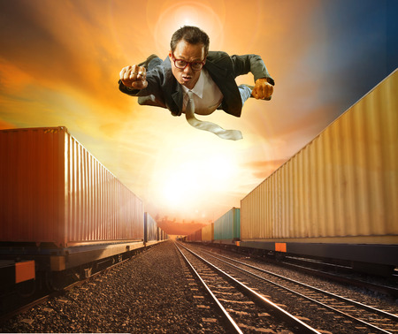 flying man: business man flying and industry container trainst running on railways track against beautiful sun set sky use for land transport and logistic business