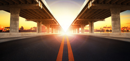 infra construction: sun rising behind perspective on bridge ram construction and asphalt raod perspective to ship port background use for infra land and vessel transportation
