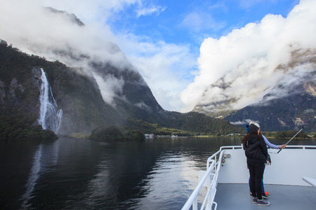 land scape: traveler take a photograph by smart phone on milford cruise ship againt beautiful natural land scape in milford sound fiord land national park new zealand