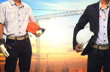 land management: two engineer man working with white safety helmet against crane and  building construction site use for civil engineering and construction industrial business