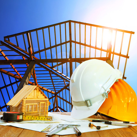 safety at work: architect working table hard hat house model plan sheet and writing equipment against home roof structure construction site Stock Photo