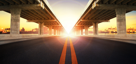 tollway: sun rising behind perspective on bridge ram construction and asphalt raod perspective to ship port background use for infra land and vessel transportation