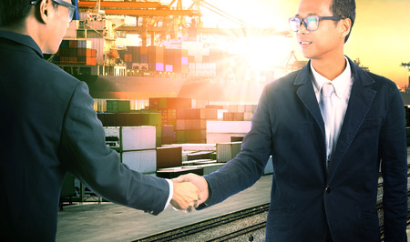 joint venture: business man successful shake hand with joint venture corperation in commercial shipping import export trading Stock Photo