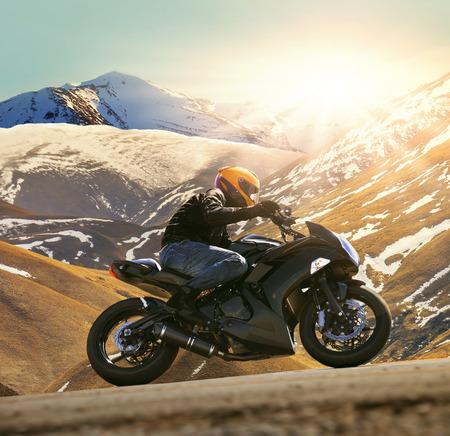 태양 스포츠, 남성 레저 및 여행 테마 빛나는 산 배경을 이용하여 아스팔트 국가로에 오토바이를 타고 젊은 사람 스톡 콘텐츠