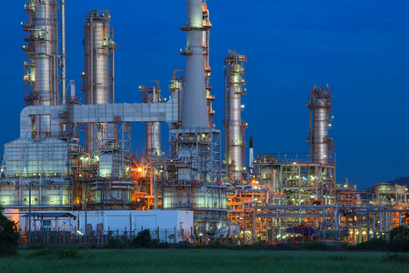 power plant: beautiful lighting of oil refinery palnt against dusky blue sky of oil refinery plant in heavy petrochemical industry estate Editorial