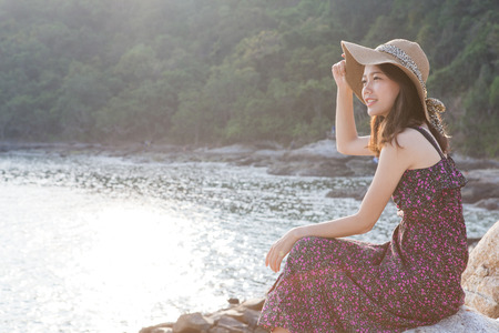 younger: portrait of young beautiful woman wearing long dress and wide straw hat smiling at sea side location use for modern life fashion and people activities on vacation Stock Photo