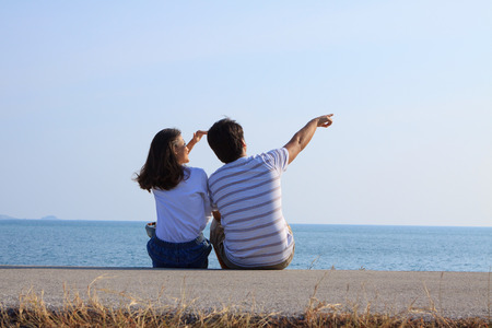 people relax: couples of man and woman sitting at sea side and point and looking to blue sky