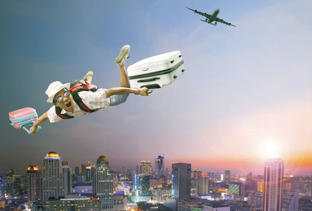 mid air: younger man flying mid air with belonging luggage and passenger plane over beautiful scenic of sky scrapper at dusky time