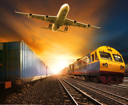 trains: industry container trainst running on railways track and cargo freight plane flying above against beautiful sun set sky use for land transport and logistic business Stock Photo