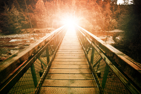 warp light at the end of suspension bridge crossing steam in wilderness