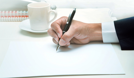 body writing: hand of business man writing by pen on empty white papeer ,top table shot business theme