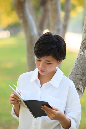 younger: younger woman  reading book in park Stock Photo