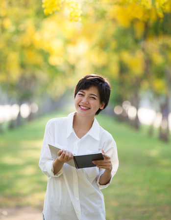 satisfies: portrait of young asian woman and book in hand rising hand as victory with happiness face emotion use for people success in education and business