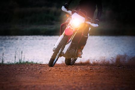 super cross: enduro motorista de la motocicleta de diapositivas en movimiento en el campo de la suciedad