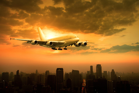 air transport: passenger jet plane flying over urban scene against beautiful sun set sky use for air transport and traveling theme