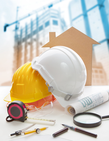 heavy construction: safety helmet blue print plan and construction equipment on architect ,engineer working table with building construction crane background use for construction industry business and civil engineering