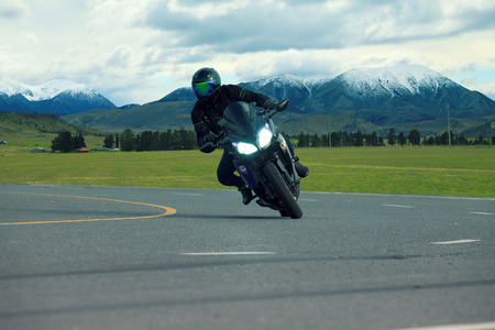 young man riding big bike motorcycle on asphalt highways use for people leisure vacation traveling and lifestyle activties
