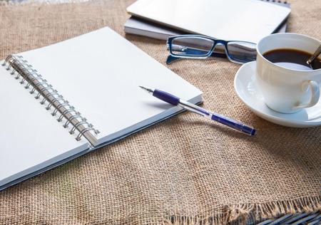 空の紙、ペン、テラスのテーブルの上にコーヒー