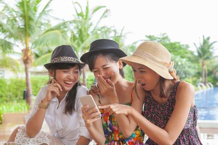女友達のスマート フォンを見ていると幸せ顔で笑ってリラックスした人々 のライフ スタイルの休暇のグループ