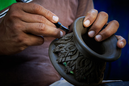 clay craft: close up potter artist working on clay pottery sculture fine art in thailand
