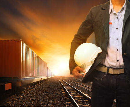 land use: industry container trainst running on railways track and working man use for land transport and logistic business