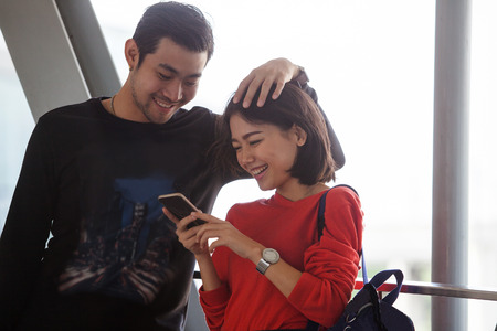 young asian couple: couples of younger asian man and woman relaxing with happy face reading text on smart phone use for people and modern lifestyle