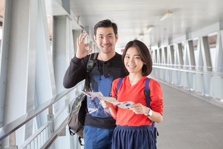 mochila de viaje: joven hombre asiático que viaja y mujer de pie con la cara sonriente con dientes suspiro bien por Sue mano aceptable para la gente moderna Backpacker que viaja de vida
