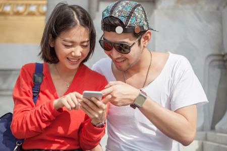 若い男と女がスマート フォン画面用デジタル技術や若者のライフ スタイルの現代人のライフ スタイルを探して 写真素材
