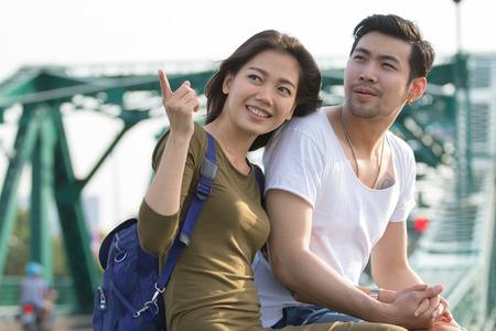 ragazza innamorata: coppie di giovane uomo e donna asiatica che si distende con la faccia felice su tirp vacanza